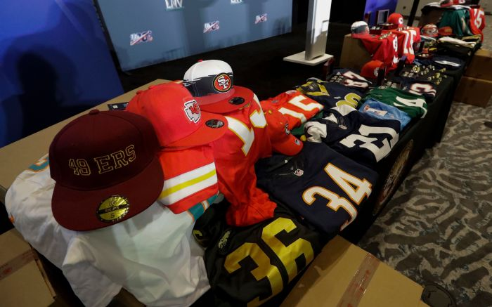 Counterfeit game-related merchandise is displayed before a news conference about seized items related to the NFL Super Bowl 54 football game, in Miami Beach, FlaSuper Bowl Football, Miami Beach, USA - 30 Jan 2020