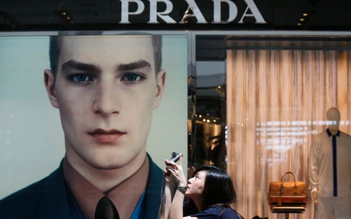 A woman takes pictures at a Prada store in Hong Kong . Italian fashion house Prada SpA plans to raise up to $2.6 billion in a listing on Hong Kong's stock exchange, according to a person familiar with the deal, joining other foreign companies flocking to cash in on China's rising fortunesHong Kong Prada IPO