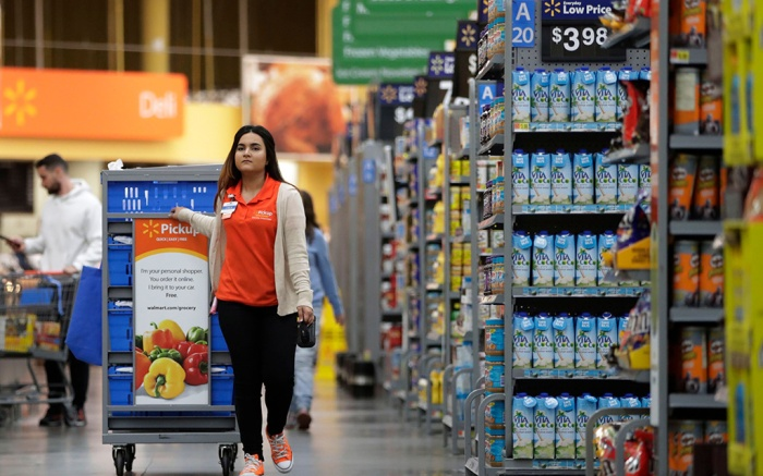 Laila Ummelaila, a personal shopper at the Walmart store in Old Bridge, N.J., pulls a cart with bins as she shops for online shoppers. Personal shoppers collect items on online orders and greet customers at a pickup location in the parking lotFuture of Work-Changing Retail, Old Bridge, USA - 08 Nov 2017