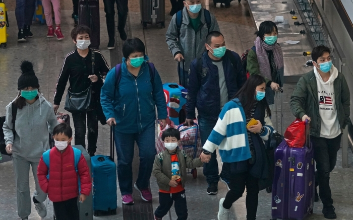 Passengers wear protective face masks arrive at the high speed train station in Hong Kong, . Hong Kong's leader has announced that all rail links to mainland China will be cut starting Friday as fears grow about the spread of a new virusChina Outbreak, Hong Kong, Hong Kong - 28 Jan 2020