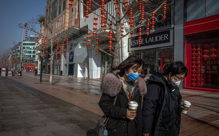 People wearing protective face masks walk down an empty shopping street in Beijing, China