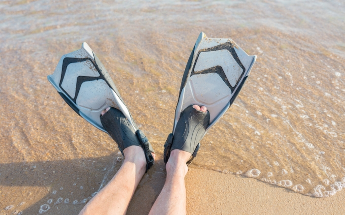 Diving fins on the sand. Summer activities, sport concept; Shutterstock ID 1455232655; Usage (Print, Web, Both): Web; Issue Date: 2/3