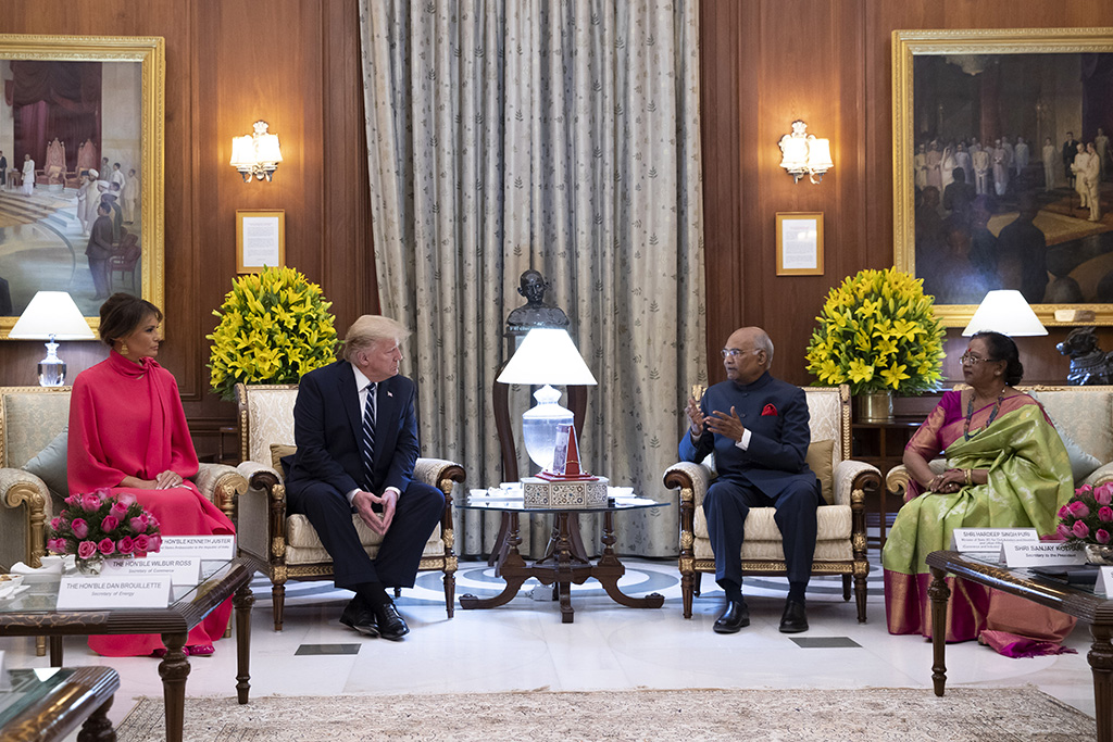U.S.President Donald Trump and first lady, Melania Trump, carolina herrera dress, hot pink flats, celebrity style, are seated with Indian President Ram Nath Kovind and his wife Savita Kovind as they arrive for a state banquet at Rashtrapati Bhavan, Tuesday, Feb. 25, 2020, in New Delhi, India. (AP Photo/Alex Brandon, Pool)