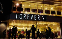 Shoppers walk by a Forever 21