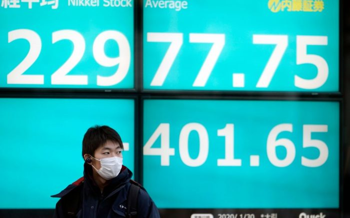 A man wearing a mask stands in front of a stock market indicator board in Tokyo, Japan, 30 January 2020. The 225-issue Nikkei Stock Average plunged 401.65 points, or 1.72 percent, to close at 22,977.75, following rising concerns over the impact on the global economy of the coronavirus outbreak in China. According to health authorities the number of known coronavirus cases jumped to 7,771 in China on 30 January including the first confirmed case in Tibet. At least 170 people have died from the virus.Tokyo stocks fall as coronavirus concerns escalate, Japan - 30 Jan 2020