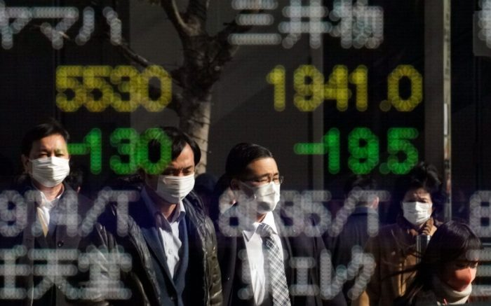 Pedestrians wearing masks are reflected in a stock market indicator display board in Tokyo, Japan, 03 February 2020. The 225-issue Nikkei Stock average hit a three-month low during the morning trading session, following rising concerns over the impact of the novel coronavirus' impact on the global.Stocks fall as coronavirus concerns escalate, in Tokyo, Japan - 03 Feb 2020