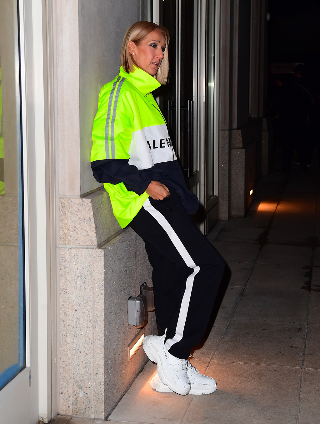 Celine Dion , balenciaga track suit, balenciaga triple s sneakers, was spotted looking youthful in a Neon Balenciaga Windbreaker as she headed back to her hotel following her 2nd NYC Concert. She wore head to toe Balenciaga, opting for a sporty look with the Men's jacket, and joggers with a chunky white trainer. She casually posed in an outdoor chair in the Hotel Garden, looking half her age.Pictured: Celine DionRef: SPL5153047 010320 NON-EXCLUSIVEPicture by: DIGGZY / SplashNews.comSplash News and PicturesLos Angeles: 310-821-2666New York: 212-619-2666London: +44 (0)20 7644 7656Berlin: +49 175 3764 166photodesk@splashnews.comWorld Rights, No Portugal Rights