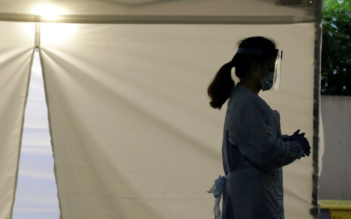 A nurse wears a protective face shield at a drive-up coronavirus testing station