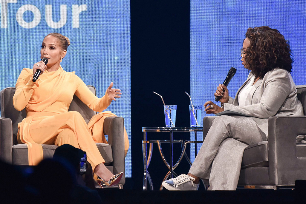 "Jennifer Lopez, oprah 2020 vision tour, sally lapointe spring 2020, orange suit, gold pumps, christian louboutin heels, Jennifer Lopez, Oprah Winfrey. Jennifer Lopez, left, and Oprah Winfrey participate in ""Oprah's 2020 Vision"" tour at the Forum, in Inglewood, CalifOprah's 2020 Vision Tour - LA, Inglewood, USA - 29 Feb 2020"