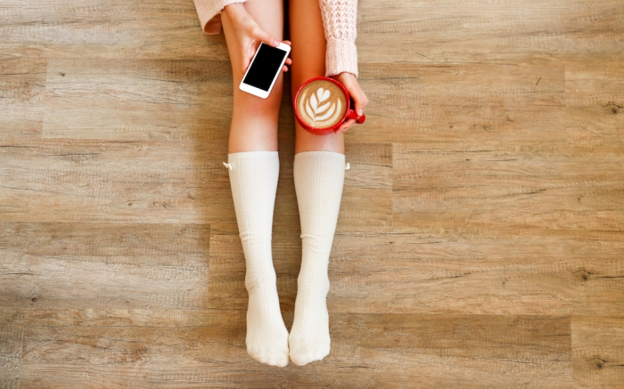 Lazy afternoon concept. Young woman wearing knee high socks, knitted sweater, sitting on wooden floor, holding blank screen mobile phone, red cup of coffee. Background, copy space, top view, close up.; Shutterstock ID 1204999027; Usage (Print, Web, Both): Web; Issue Date: 2/3