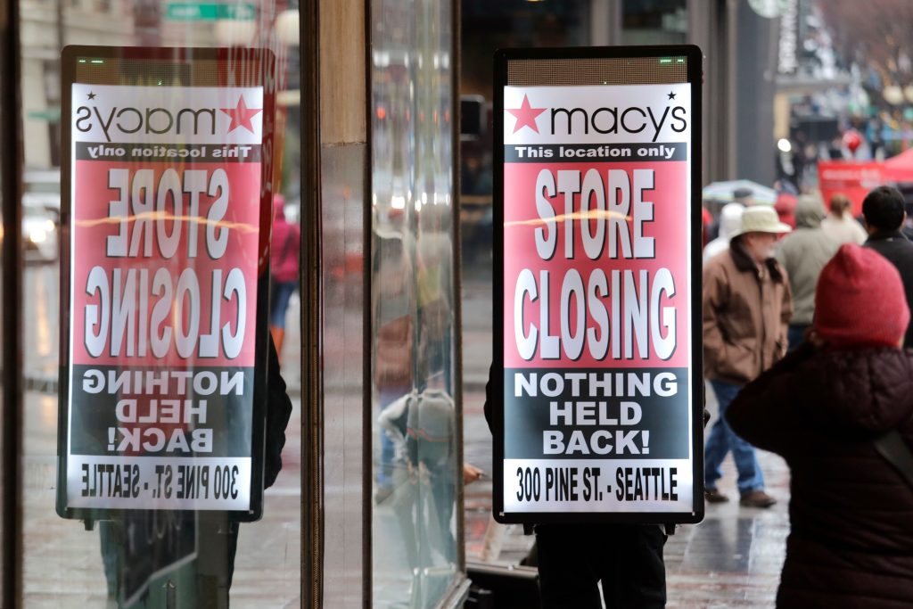 "A man walks with a ""store closing"" sign on his back in front of the Macy's store in downtown Seattle. The store is one of nearly 30 Macy's stores to be closed nationwide in the coming weeksMacys Closing, Seattle, USA - 09 Jan 2020"