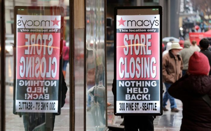 """A man walks with a """"store closing"""" sign on his back in front of the Macy's store in downtown Seattle. The store is one of nearly 30 Macy's stores to be closed nationwide in the coming weeksMacys Closing, Seattle, USA - 09 Jan 2020"""