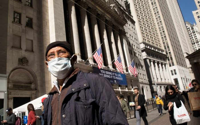 A man wears a mask as he passes the New York Stock Exchange, . The dizzying action in financial markets escalated Monday as stocks moved closer to a bear market and oil prices fell the most since 2008Financial Markets Wall Street, New York, USA - 09 Mar 2020