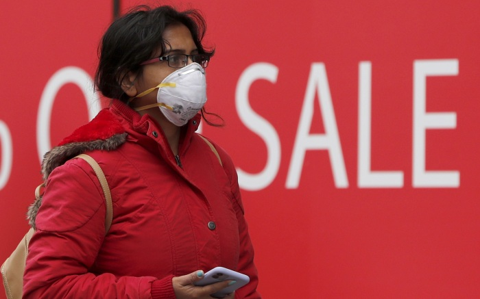 Woman wearing a face mask walks along Oxford Street in London, . For most people, the new coronavirus causes only mild or moderate symptoms, such as fever and cough. For some, especially older adults and people with existing health problems, it can cause more severe illness, including pneumoniaVirus Outbreak, London, United Kingdom - 14 Mar 2020