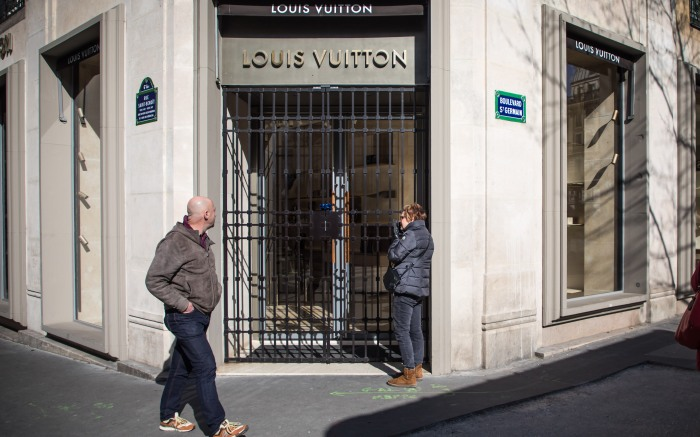 People walk by the closed Louis Vuitton luxury store in the Latin Quarter district, as part of the measures to contain the spread of coronavirus SARS-CoV-2 which causes the Covid-19 disease, in Paris, France, 15 March 2020. French Prime Minister Edouard Philippe announced on 14 March 2020 that all places that are not essential to French living, including restaurants, cafes, cinemas and clubs, will be closed from 15 March 2020 until further notice. President Macron announced the closing of schools, high schools and nurseries from 16 March 2020 on.Closed doors due to coronavirus crisis, Paris, France - 15 Mar 2020