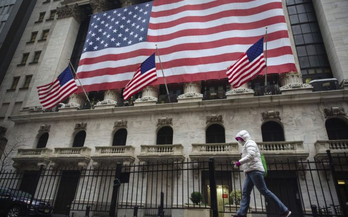 Pedestrian wearing a surgical mask and gloves walks past the New York Stock Exchange, in New York. Stocks are swinging between gains and losses in early trading on Wall Street Thursday, but the moves are more subdued than the wild jabs that have dominated recent weeks. At least for nowFinancial Markets Wall Street, New York, United States - 19 Mar 2020