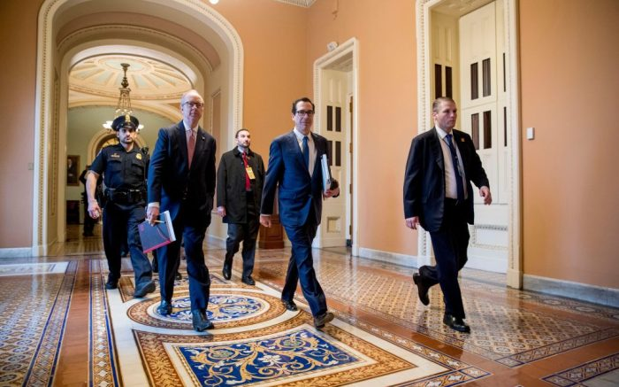 Treasury Secretary Steven Mnuchin, center, and White House Legislative Affairs Director Eric Ueland, second from left, walk to the offices of Senate Majority Leader Mitch McConnell of Ky. on Capitol Hill in Washington, as the Senate is working to pass a coronavirus relief billVirus Outbreak Congress, Washington, United States - 23 Mar 2020