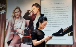 A woman passes an advertisement for