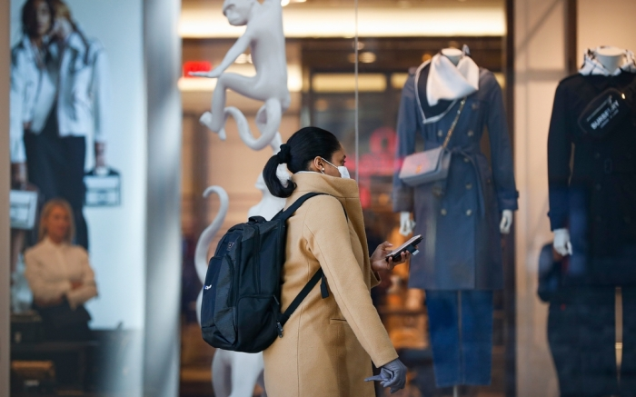 Pedestrian wearing a face mask passes a retail store as an attendant looks, in New York. New York leaders took a series of unprecedented steps Sunday to slow the spread of the coronavirus, including canceling schools and extinguishing most nightlife in New York CityVirus Outbreak , New York, United States - 16 Mar 2020
