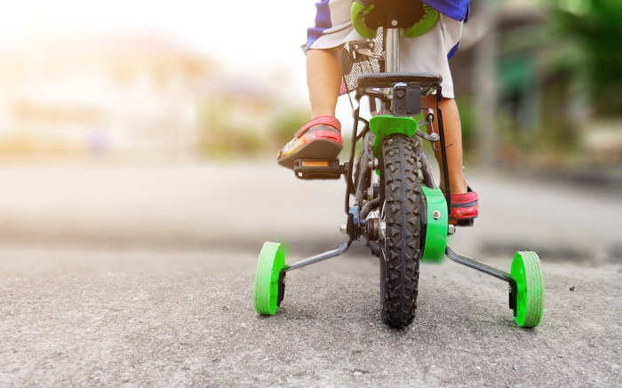 Learning to ride a bike concept, The little boy is practicing cycling a bicycle with the training wheels on the road.; Shutterstock ID 1175636098; Usage (Print, Web, Both): web; Issue Date: 4/9