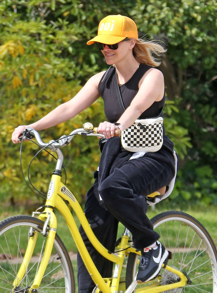 Reese Witherspoon, sweatpants, baseball cap, sunglasses, nike daybreak sneaker,s rides her bike in Los Angeles.Reese Witherspoon out and about, Los Angeles - 31 Mar 2020