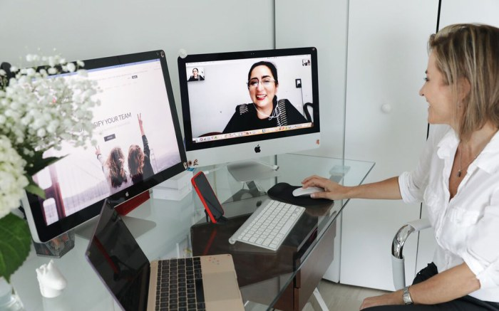 Woman works from home with multiple monitors and screens