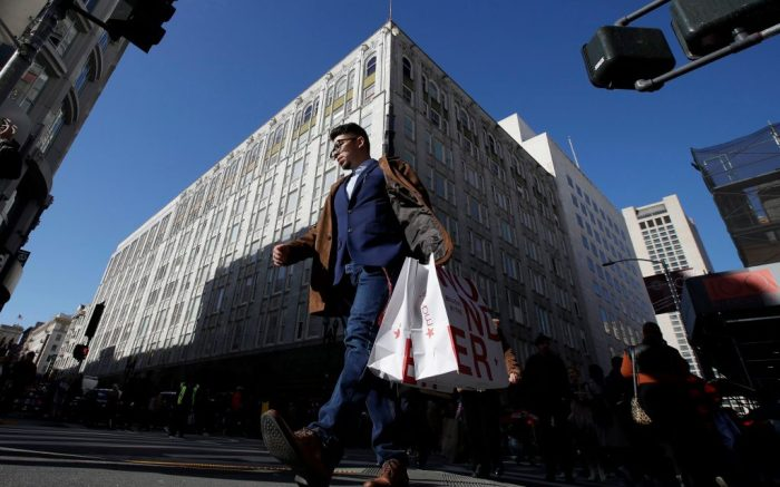 A man carries shopping bags across the street from a Macy's store in San Francisco, . Black Friday once again kicked off the start of the holiday shopping seasonBlack Friday Shopping, San Francisco, USA - 29 Nov 2019