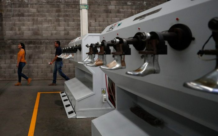 People walk inside the Tenis Court shoe factory in Leon, Guanajuato state, Mexico. Mexico's drug war has long played out in dusty northern border cities or the poppy fields of its southern mountains, but now the killings have moved to the conservative industrial heartland state, creating a strange duality: booming foreign investment even as the state becomes Mexico's most violentIndustry and Violence, Leon, Mexico - 13 Feb 2020