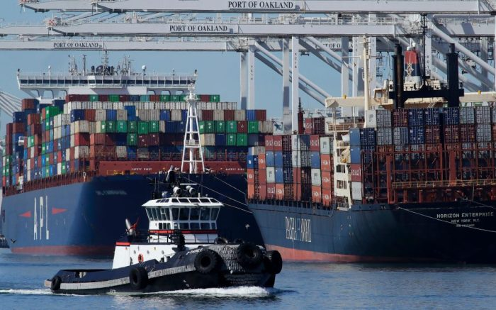 A tugboat passes container ships being unloaded at the Port of Oakland, in Oakland, CalifContainer Shipping, Oakland, USA - 04 Mar 2020