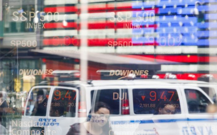 People are seen reflected in window with the values of the Nasdaq composite and Dow Jones industrial averages shown on a screen in Times Sqaure in New York, New York, USA, 16 March 2020. Stocks opened sharply lower this morning and trading was halted for 15 minutes at the opening bell as investors continue to react to the impact of the COVID-19 coronavirus pandemic.New York Stock Exchange Coronaviurus reaction, USA - 16 Mar 2020