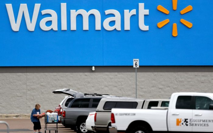 Woman pulls groceries from a cart to her vehicle outside of a Walmart store, in Pearl, MissVirus Outbreak Mississippi Daily Life, Pearl, United States - 31 Mar 2020