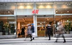 Shoppers pass a H&M (H &