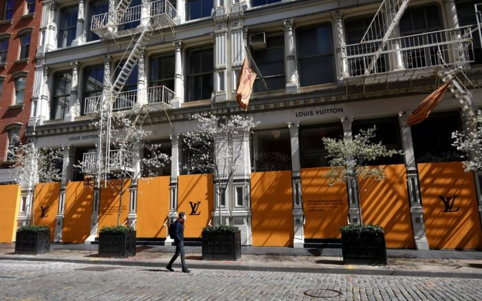 A man walks past a boarded up Louis Vuitton New York SOHO store in the SOHO neighborhood in New York, New York, USA, 11 April 2020. New York City is still considered the epicenter of the coronavirus outbreak in the United States and people are still being asked to stay at home to stop the spread of the coronavirus and minimize the number of COVID-19 patients needing medical attention.Coronavirus in New York, USA - 11 Apr 2020
