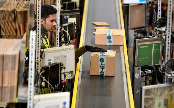 A worker puts a parcel on a belt at the giant storehouse of the Amazon Logistic Center in Rheinberg, Germany, . Amazon in Rheinberg hired extra workers for the Christmas salesAmazon, Rheinberg, Germany - 14 Nov 2018
