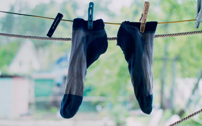 The washed socks are hung on the rope. Dry socks are dried on the street.Hanging clothes drying outdoors; Shutterstock ID 1396286216; Usage (Print, Web, Both): web; Issue Date: 4/9