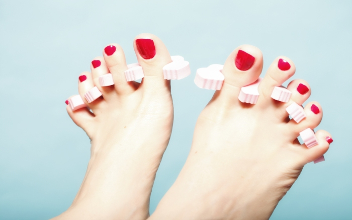 foot pedicure applying woman's feet with red toenails in pink toe separators blue background; Shutterstock ID 161448680; Usage (Print, Web, Both): web; Issue Date: 4/9