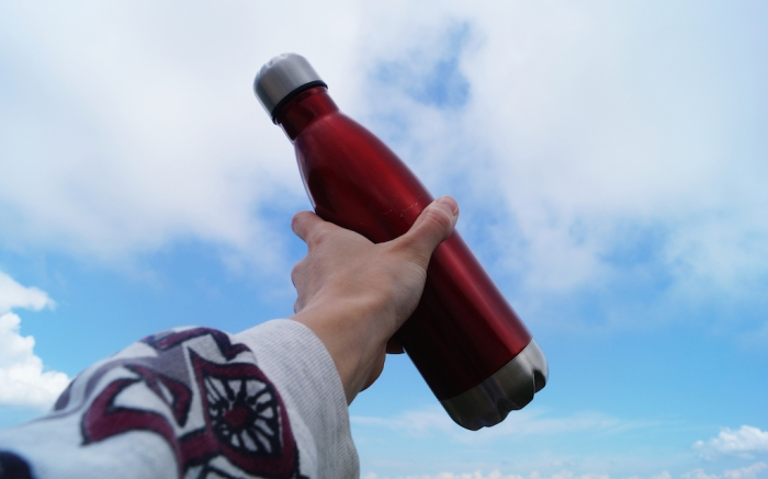 Close-up of red metal bottle for water in a female hand on a cloudy blue sky background.  Mountain landscape. Life style and travel concept. Zero waste. Ecology. Plastic free. Place for text. ; Shutterstock ID 1486606112; Usage (Print, Web, Both): web; Issue Date: 4/9