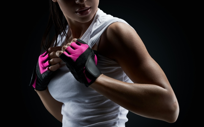 Close up portrait of female bodybuilder wearing gloves ready for gym exercise. Horizontal studio shot with copy space on black background; Shutterstock ID 454516888; Usage (Print, Web, Both): web; Issue Date: 4/9