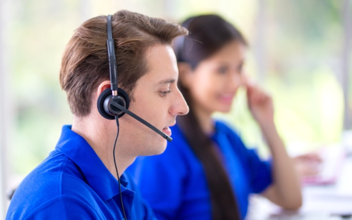two customer service agents on headsets fieling requests