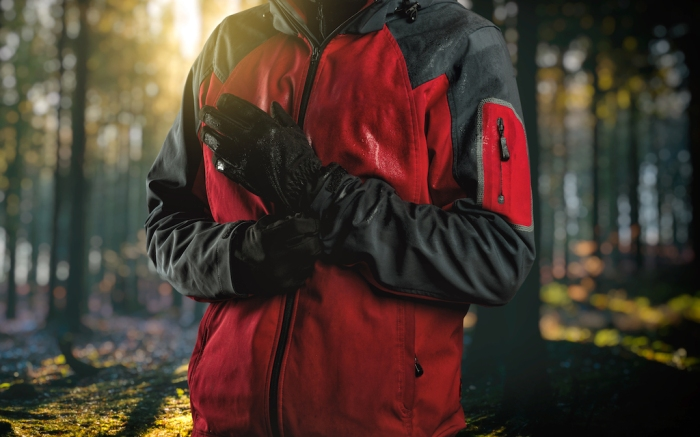 Man wearing outdoor clothing, close up (hardshell waterproof jacket and softshell) standing with gloves on hands  - exploring and adventure concept. Forest in background; Shutterstock ID 505209163; Usage (Print, Web, Both): web; Issue Date: 4/9