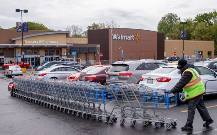 A Walmart employee collects shopping carts in the parking lot during the COVID-19 coronavirus pandemic at a Walmart in Alexandria, Virginia, USA, 01 May 2020. Workers from corporations, including employees from Amazon, Walmart and FedEx, are planning a walkout asking for better health and safety standards as well as hazard pay while working during the coronavirus pandemic.Workers from corporations, including employees from Amazon, Walmart and FedEx, are planning a walkout asking for better health and safety standards as well as hazard pay while working during the coronavirus pandemic, Alexandria, USA - 01 May 2020