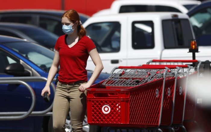 An employee wears a face mask while collecting shopping carts outside a Target store, near Brighton, Colo., during the coronavirus pandemicVirus Outbreak Colorado, Brighton, United States - 17 May 2020