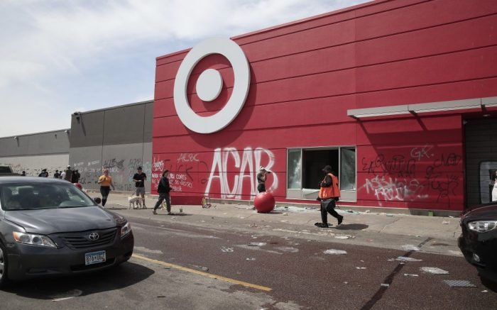People walk past a destroyed and grafitti-covered Target store after a night of rioting and vandalism which followed a second day of protests over the arrest of George Floyd, who later died in police custody, in Minneapolis, Minnesota, USA, 28 May 2020. A bystander's video posted online on 25 May, appeared to show George Floyd, 46, pleading with arresting officers that he couldn't breathe as an officer knelt on his neck. The unarmed black man later died in police custody.Police abuse protest in wake of George Floyd death in Minneapolis, USA - 28 May 2020