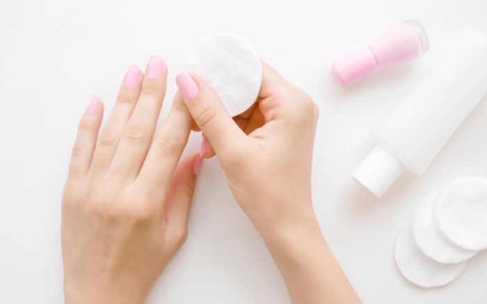 Woman's hand removing pink nail polish with white cotton pad. Point of view shot. Closeup.; Shutterstock ID 1396740467; Usage (Print, Web, Both): web; Issue Date: 4/9