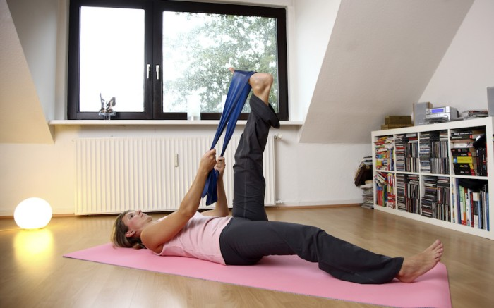 MODEL RELEASED Young woman exercising with a resistance band, Deuser band, at home, stretching exercisesVARIOUS