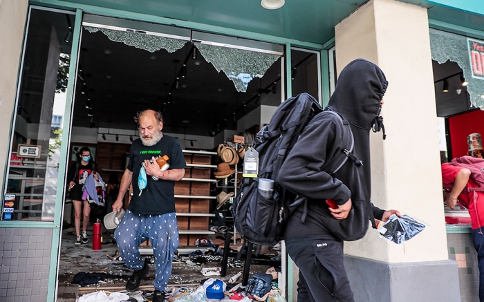 Looters plunder the Sand and Surf Store as protestors face off with police as unrest continues in the wake of the death of George Floyd in Minneapolis. (Robert Gauthier / Los Angeles Times)Protests after the death of George Floyd, Santa Monica, Los Angeles, California, USA - 31 May 2020
