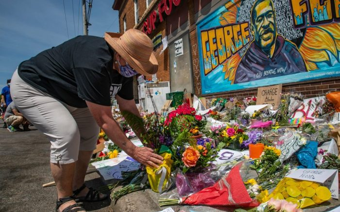 """Linda Crear, 67, from Richfield, Minn., places flowers at an organic memorial for George Floyd near the spot where he died while in police custody, in Minneapolis, Minn. """"It's overwhelming, it's so heartbreaking,"""" said Crear, """"This is a man who had a full life and it was just trashedAmerica Protests , Minneapolis, United States - 31 May 2020"""