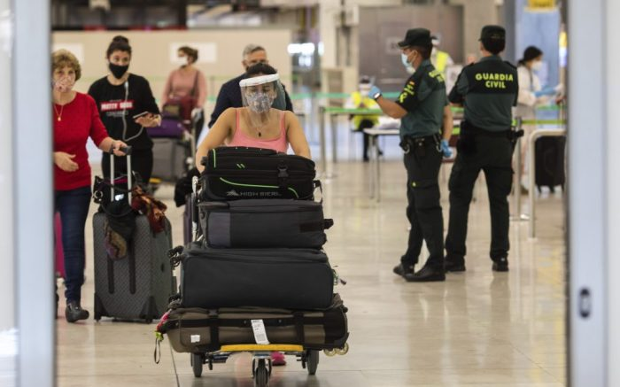 Passengers wearing face masks arrive at Adolfo Suarez-Barajas international airport, outskirts Madrid, Spain, . Spain opened its borders to European tourists on Sunday in a bid to kickstart its vital tourism economy, but Brazil and South Africa reported record new levels of coronavirus infectionsVirus Outbreak , Madrid, Spain - 21 Jun 2020