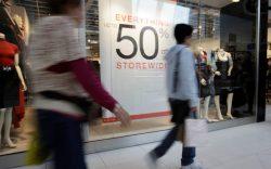 Shoppers walk past a sale sign