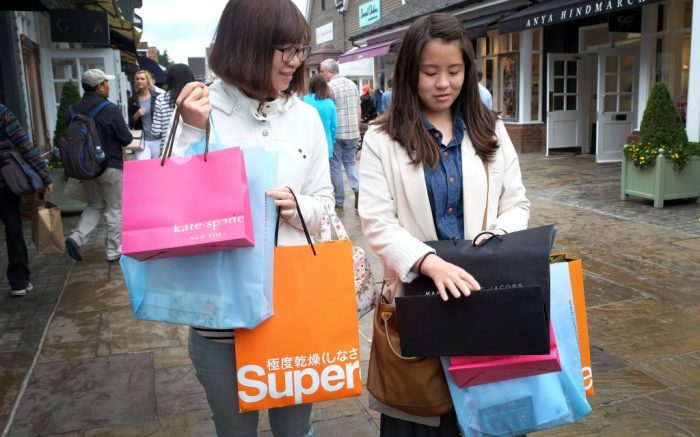 Shoppers carry designer label branded bags at Bicester Village designer outlet centre, in Bicester, England, in this photo dated . Chinese customers have become a powerful market force in the global trade in expensive clothes, jewelry, watches, perfumes and handbags, but nobody knows how the recent turmoil in Chinese financial markets will impact on the sales of designer brandsBritain Luxury Goods China, Bicester, United Kingdom
